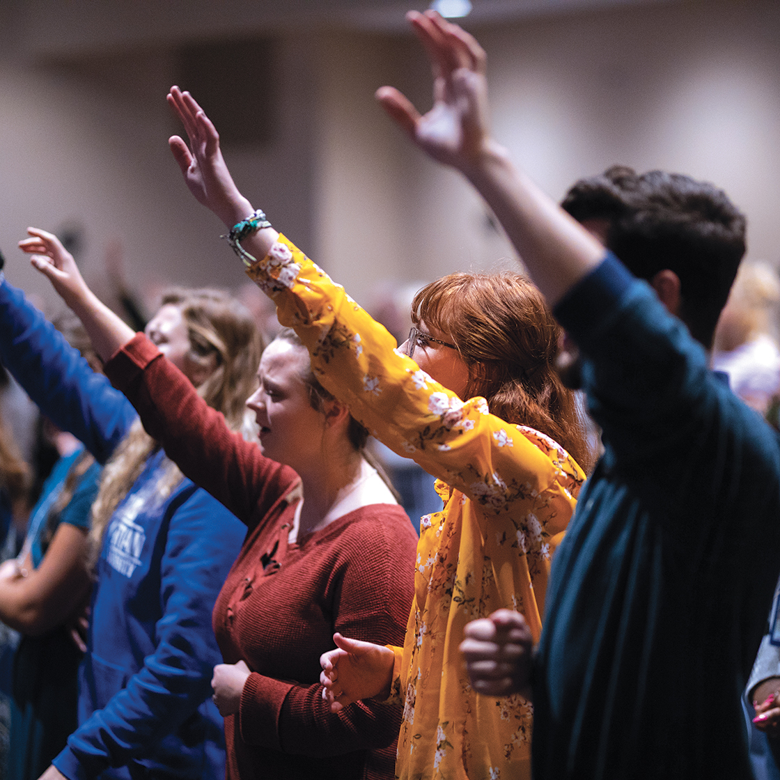 Students with hands raised in worship