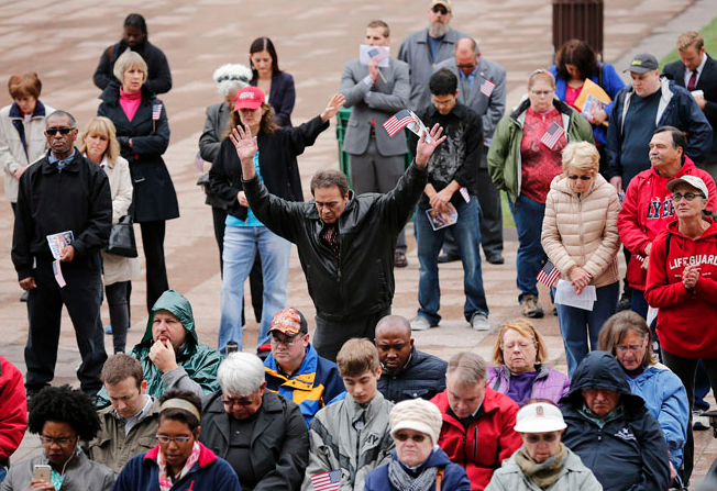 Mike Butto of the West Side raises his arms in prayer as he and dozens of other gathered for the National Day of Prayer observance ceremony on the steps of the Statehouse on Thursday